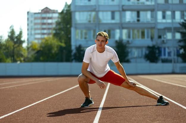 Sportliches training. junger kaukasischer sportlicher mann, männlicher athlet, läufer, der allein im öffentlichen stadion übt