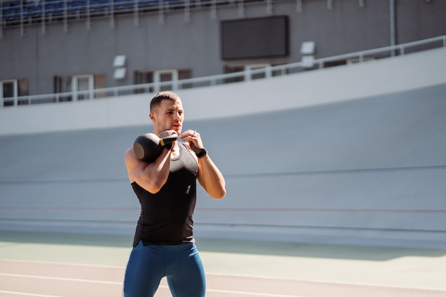 Sportliches training mit kettlebell. gutaussehender mann mit gutem körperbau. kraft und motivation.