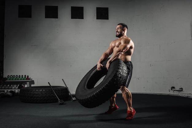Sportliches training muskulöser mann, der reifen im fitnessstudio umdreht