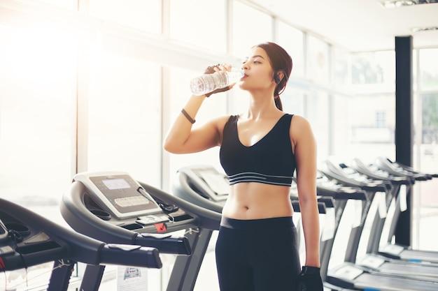 Sportliches trinkwasser frau asiens nach übungen in der turnhalle