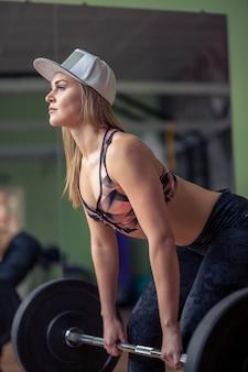 Sportliches weibliches fitnessmodell, das schwere langhantel hält und sich auf kreuzheben vorbereitet.