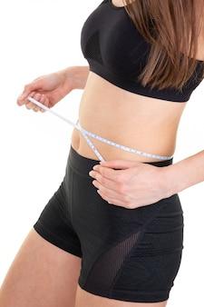 Sportmädchen, das maße ihres körpers nimmt