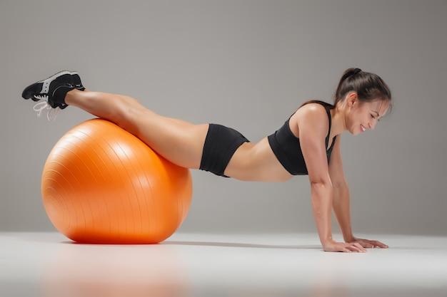 Sportmädchen, das übungen auf einem fitball macht
