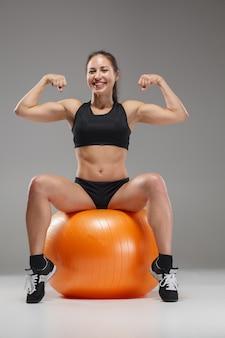 Sportmädchen, das übungen auf einem fitball tut