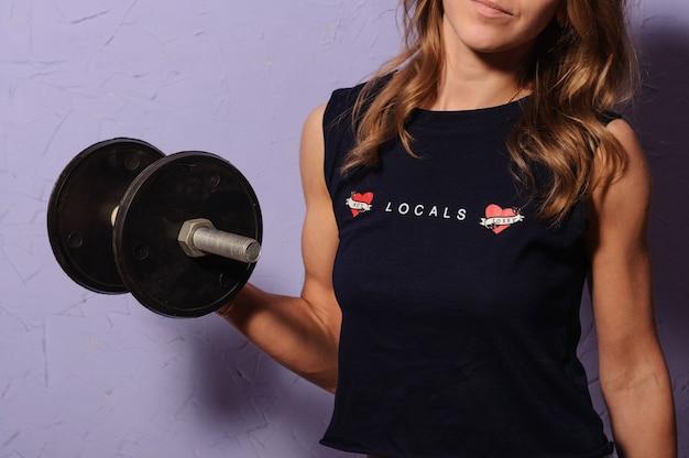 Sportmädchen in einem schwarzen hemd, das eine hantel hält