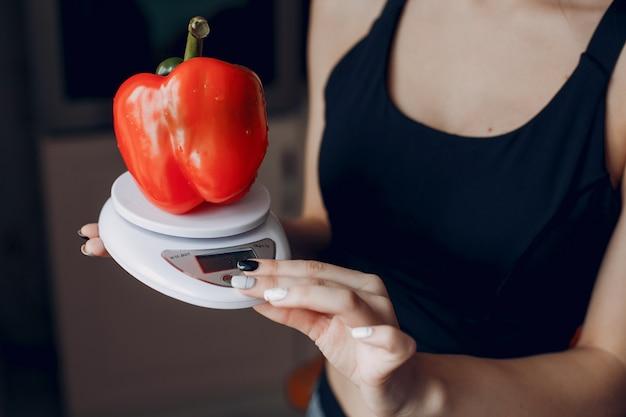 Sportmädchen in einer küche mit gemüse