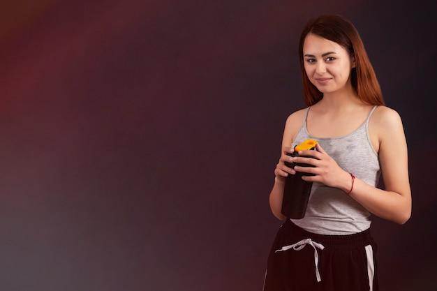 Sportmädchen nach dem spielen von sportgetränken von einem shaker
