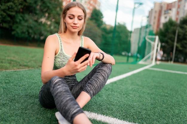 Sportmädchen sitzt und benutzt das telefon