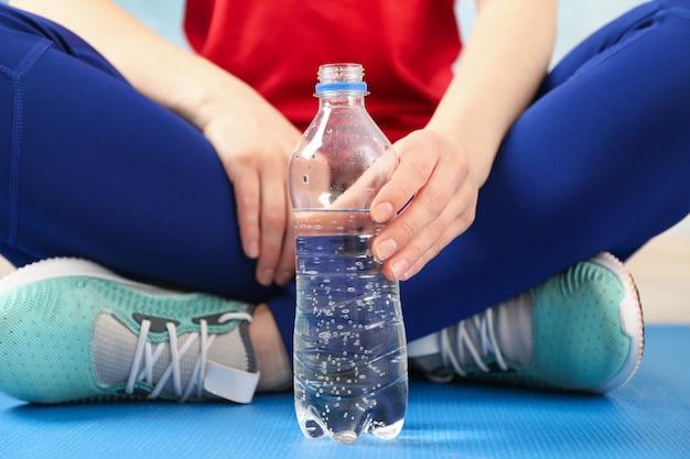 Sportmädchen sitzt und hält flasche mit wasser, nahaufnahme