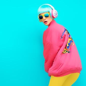 Sportmädchen-winterstil auf blauem hintergrund in hellem vintage-hoodie und exklusiven kopfhörern
