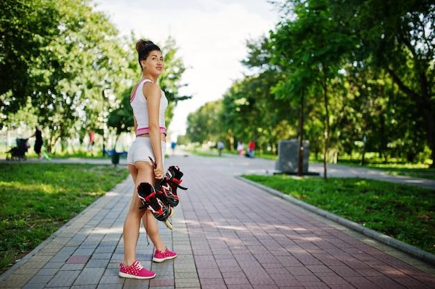 Sportmädchenabnutzung auf weißem hemd des kurzen hosenamerikanischen nationalstandards mit rollschuhen am park.