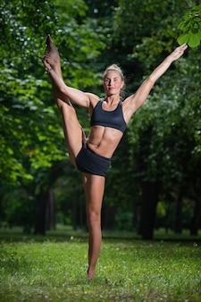 Sportmädchenakrobat führt akrobatisches element auf dem gras durch