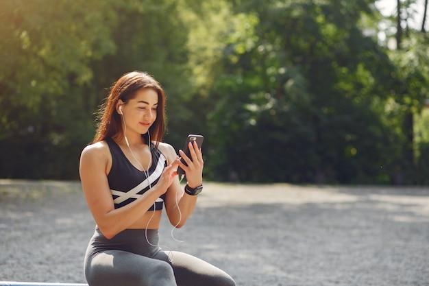 Sportmädchentraining mit telefon und kopfhörern