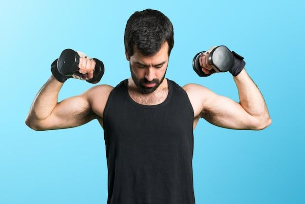 Sportman macht gewichtheben auf buntem hintergrund