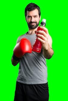 Sportman mit boxhandschuhen trinkwasser soda