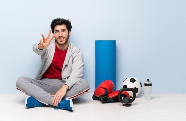 Sportmann, der auf dem boden glücklich sitzt und drei mit den fingern zählt
