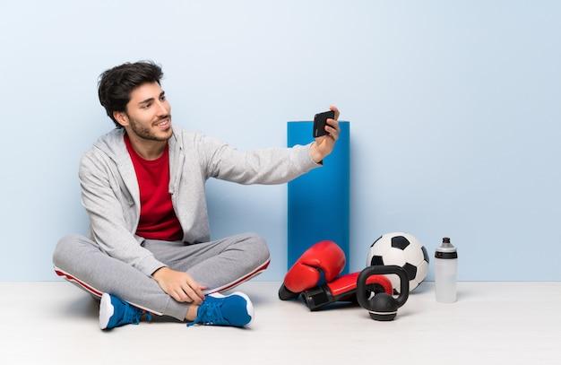 Sportmann, der auf dem boden macht ein selfie sitzt