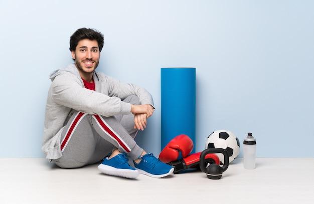 Sportmann, der auf dem boden mit den armen gekreuzt sitzt und vorwärts schaut