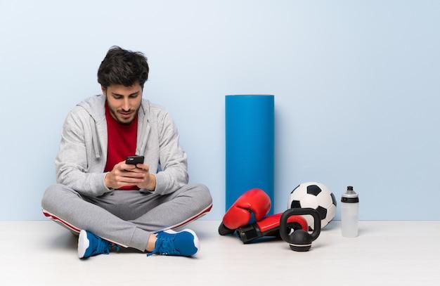 Sportmann, der auf dem boden sendet eine mitteilung mit dem mobile sitzt