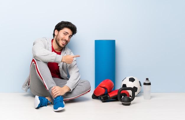 Sportmann, der auf dem boden zurück zeigt sitzt