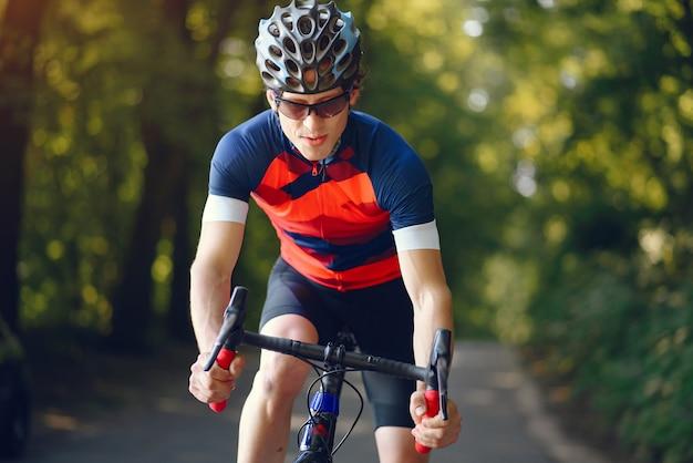 Sportmann, der fahrrad im sommerwald reitet