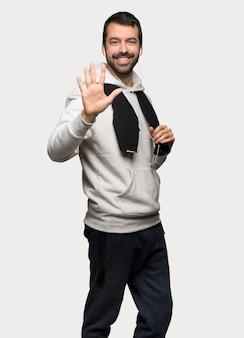 Sportmann, der fünf mit den fingern über lokalisiertem grauem hintergrund zählt