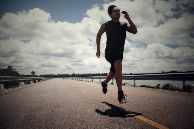 Sportmann mit läufer auf der straße läuft für die übung
