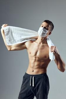 Sportmann muskulöser oberkörper weißes handtuch medizinische gesundheitsmaske fitnessstudio