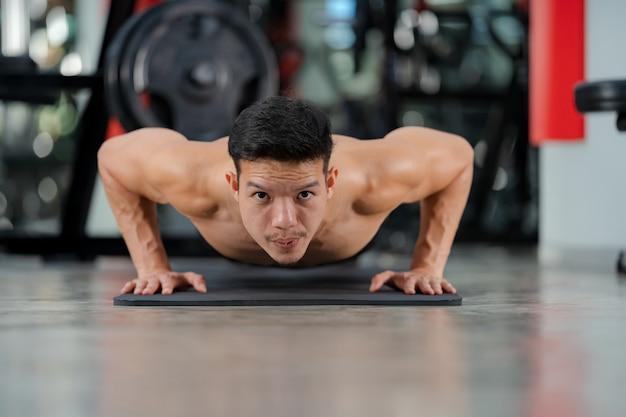 Sportmann-training, das liegestütze im fitnessstudio trainiert