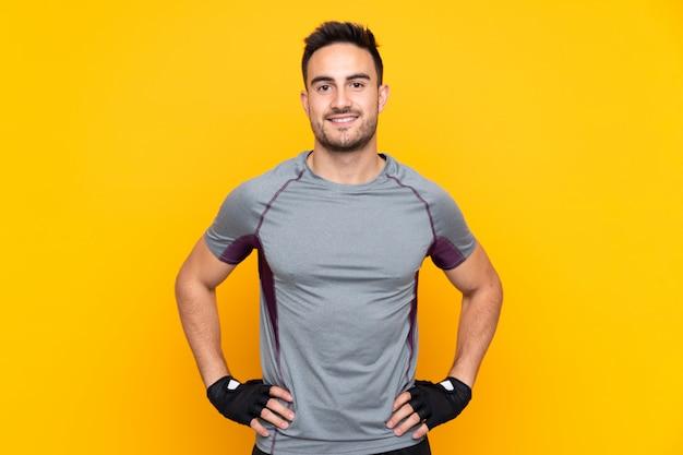 Sportmann über gelbe wand, die mit armen an der hüfte aufwirft und lächelt