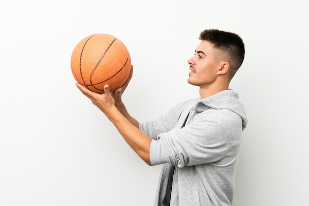 Sportmann über lokalisierter weißer wand mit ball des basketballs