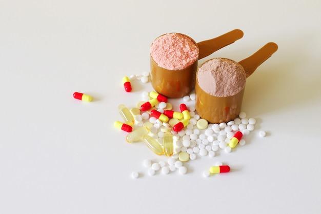 Sportmedizinische vitamine und drogen. zwei messlöffel molkeprotein
