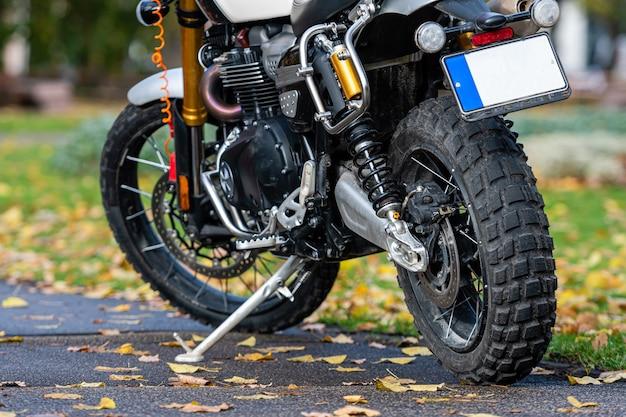 Sportmotorrad geparkt auf dem bürgersteig im park mit gelbem herbstlaub