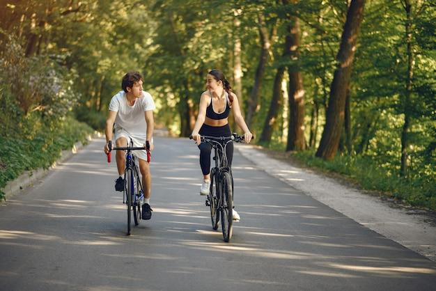 Sportpaar, das fahrräder im sommerwald reitet