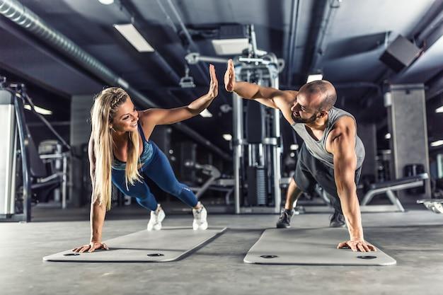 Sportpaar, das plankenübungstraining im fitnesscenter macht. mann und frau üben planke in der turnhalle.