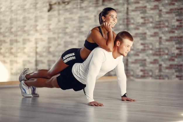 Sportpaar in einem sportbekleidungstraining in einem fitnessstudio