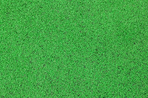 Sportplatz oder spielplatz hintergrund. künstliche gummibeschichtung für spielplätze und sportplätze in grüner farbe