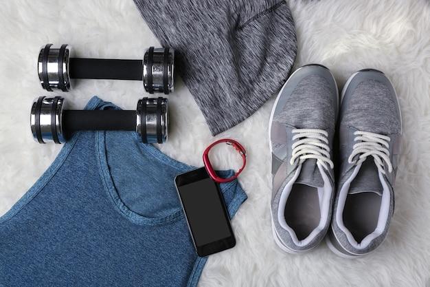 Sportsachen mit fitnesstracker und smartphone auf fell