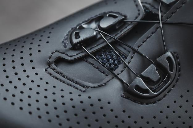 Sportschuhe aus schwarzem perforiertem leder in dunklem schlüssel. nahaufnahme