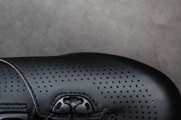 Sportschuhe aus schwarzem perforiertem leder in dunklem schlüssel.