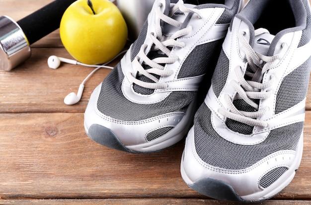 Sportschuhe mit hantel und kopfhörern auf holztisch