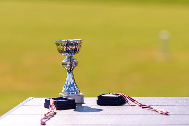 Sportspielpreise - pokal und medaillen auf unscharfem hintergrund, nahaufnahme