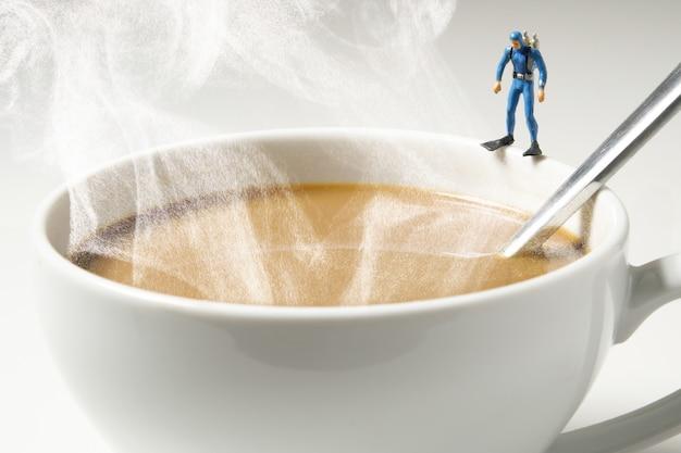 Sporttaucher-miniaturmann, der auf weißer kaffeetasse steht