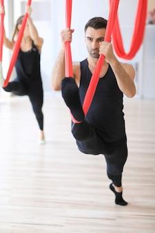 Sporttrainer machen stretching-aktivitäten mit bettwäsche