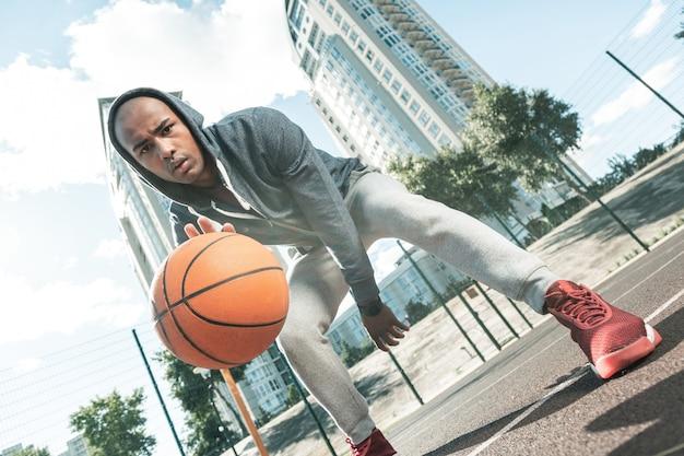 Sporttraining. angenehmer junger mann, der zum sportplatz kommt, während er trainiert, um basketball zu spielen