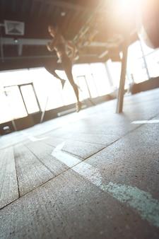 Sporttrainingskonzept vertikale aufnahme einer athletischen frau in sportbekleidung, die im industriellen fitnessstudio trainiert