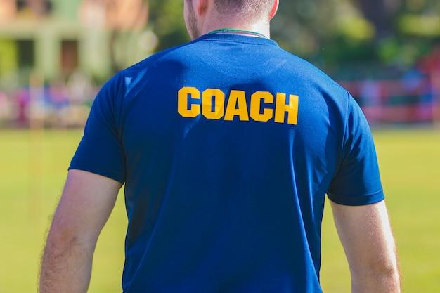 Sporttrainingstrainer im blauen hemd mit gelbem trainertext auf der rückseite
