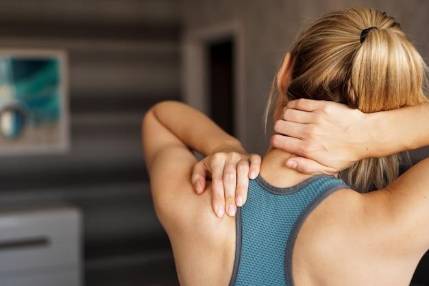 Sportverletzungskonzept. sportliches mädchen, das schmerz in ihrem nacken gegen unschärfe fühlt. schmerzen nach dem training zu hause