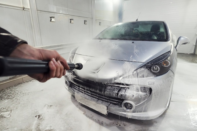 Sportwagen mit hochdruckwasser reinigen. mann, der sein auto unter hochdruckwasser im dienst wäscht. mann arbeiter wäscht das auto. selbstbedienung