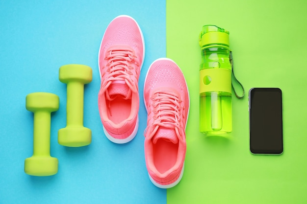 Sportwasserflasche, schuhe, handy und hanteln auf farbe